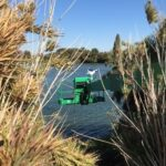 Chemical treatment of arundo at a steep shoreline from an aerial boom lift hanging over the water.