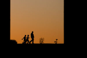 The silhouettes of an adult and two children walking in the Delta after sunset.