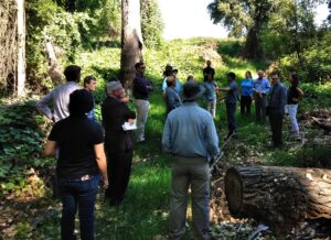 A group of 19 people observing a restoration project site while listening to a man speaking.