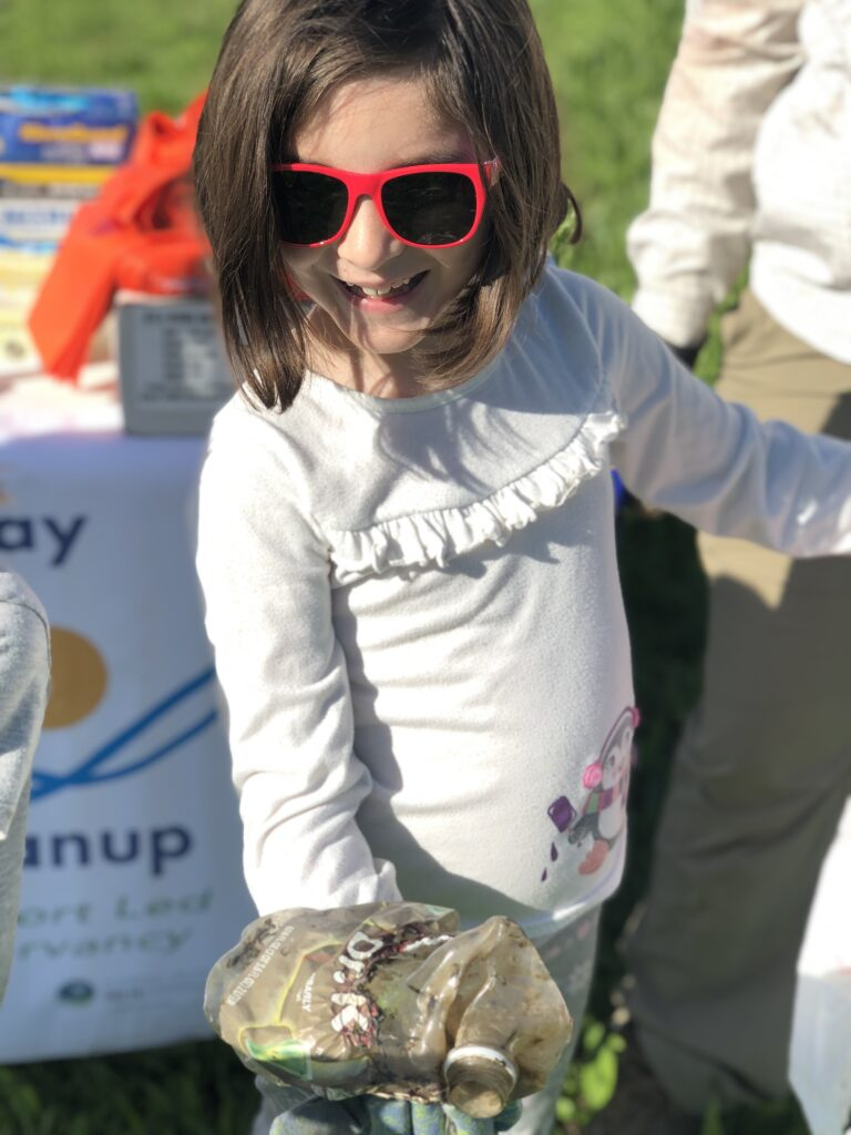 A young girl wearing red sunglasses and blue gloves holding up an old plastic soda bottle toward the camera during a Waterway Cleanup.