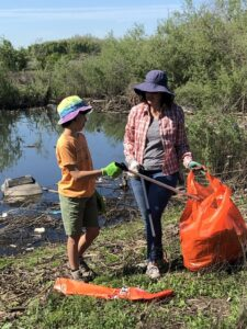 An adult woman and a young boy near a creek using trash grabbers to place trash into a large orange plastic trash bag.