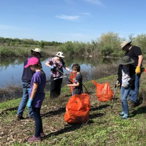 Six people, adults and children, standing outside next to a creek using trash grabbers to place trash into large orange plastic trash bags.
