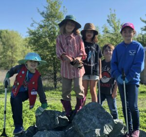Five children, some wearing gloves and some holding trash grabbers, smiling at the camera while standing on a pile of grey rocks in the middle of the green grass at the Waterway Cleanup.
